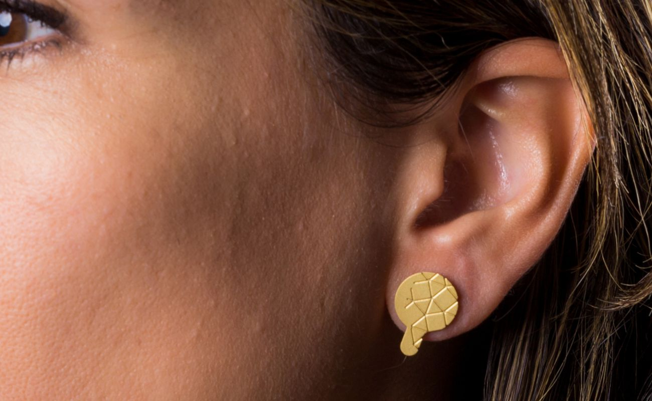 Empreinte II earrings gold matt finish placed on ear