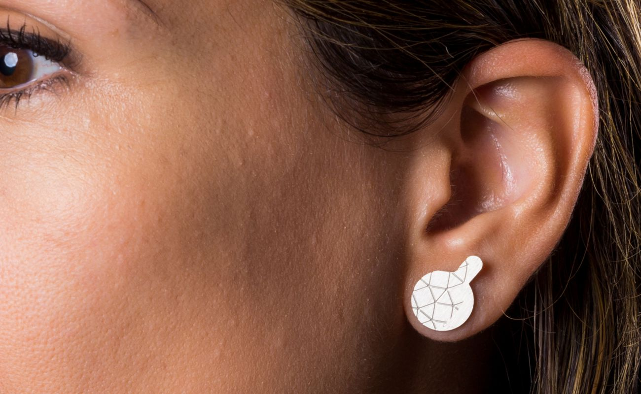 Empreinte II earrings finished in frosted silver placed on ear