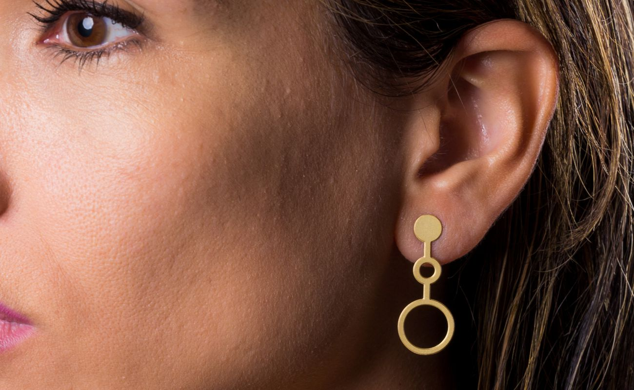 View of Ondes earrings in brass golden finish placed on ear