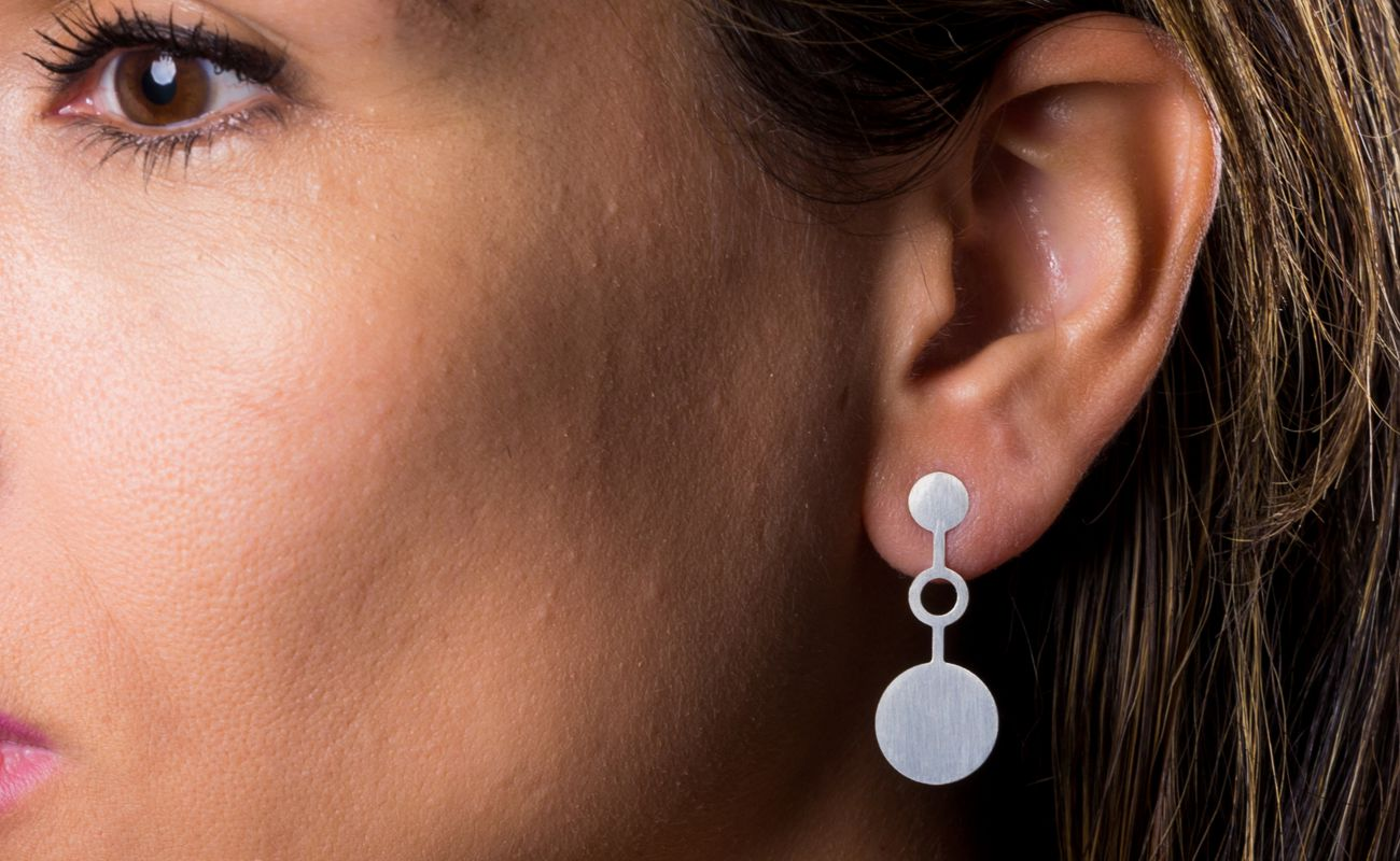 View of Ondes earrings in brass silver finish placed on ear