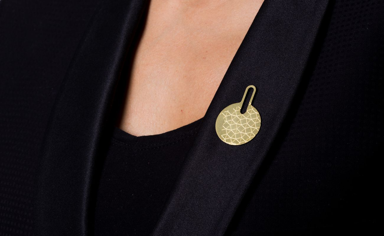 Brooch gold-plated finish on lapel.