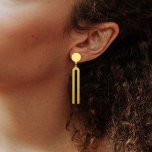 Diapason earring in brass golden finish placed on ear